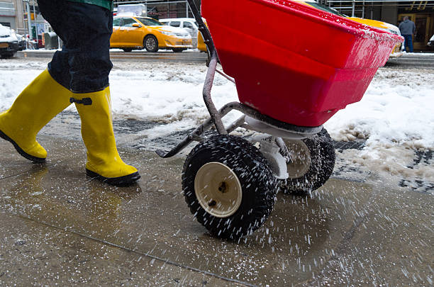 worker spreading salt on icy sidewalk - smelten stockfoto's en -beelden