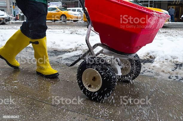 Photo of Worker spreading salt on icy sidewalk