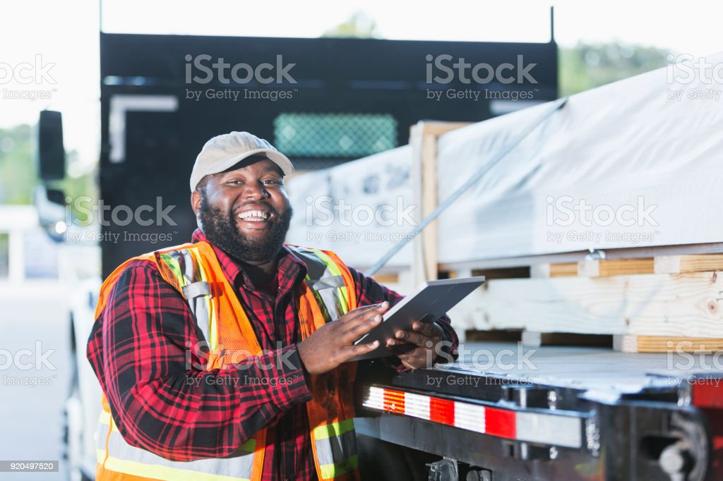 Worker standing by truck loaded with building material stock photo