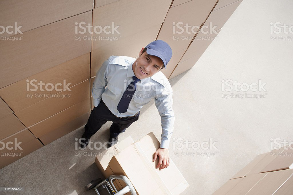 Worker standing with boxes and hand truck royalty-free stock photo