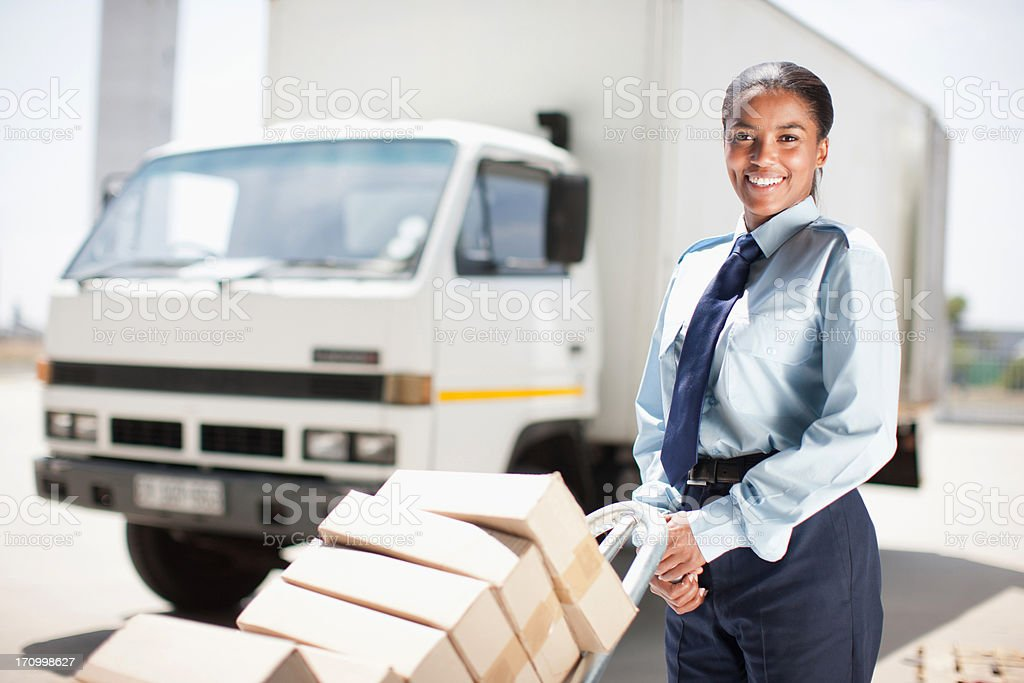 Worker standing with stack of boxes stock photo