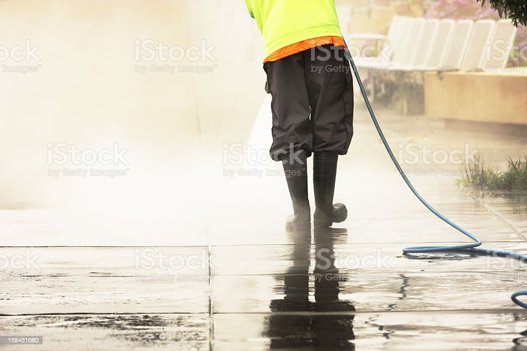 Worker Steam Cleans Sidewalk royalty-free stock photo