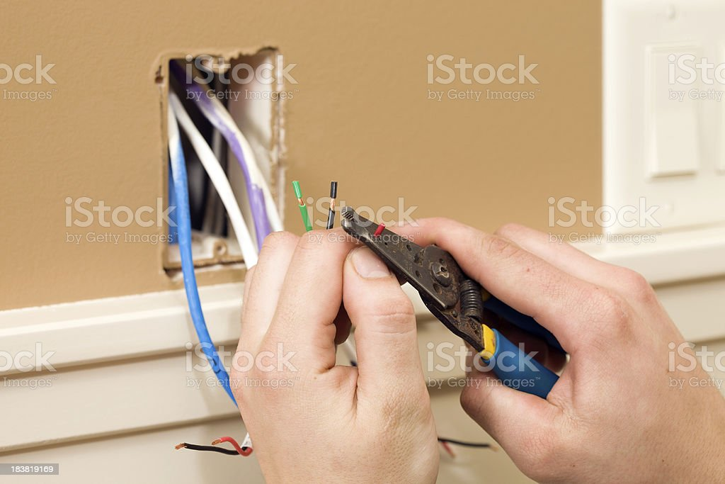 Worker Stripping Wire for Ceiling Speaker Control stock photo