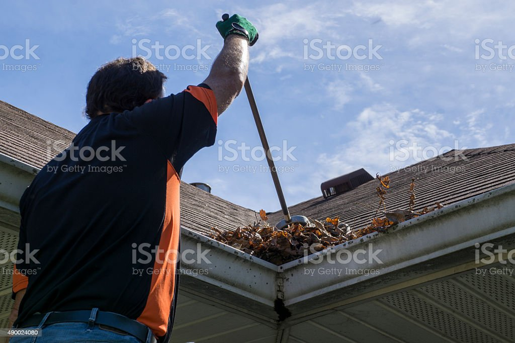 Worker Sweeping Leaves From Roof Valley stock photo