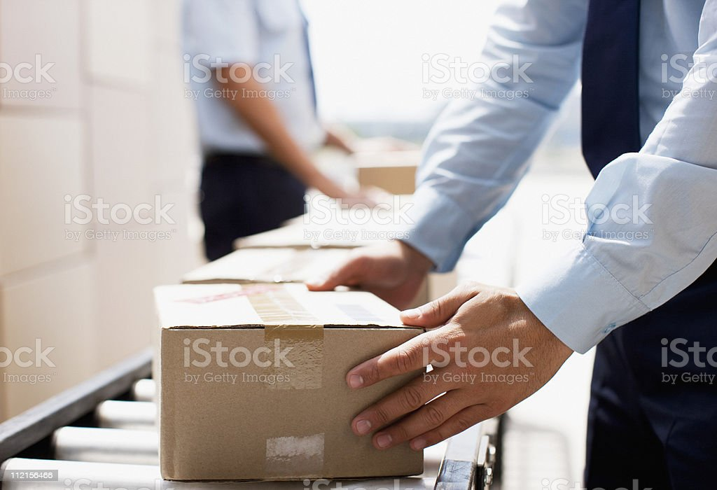 Worker taking box from conveyor belt in shipping area royalty-free stock photo
