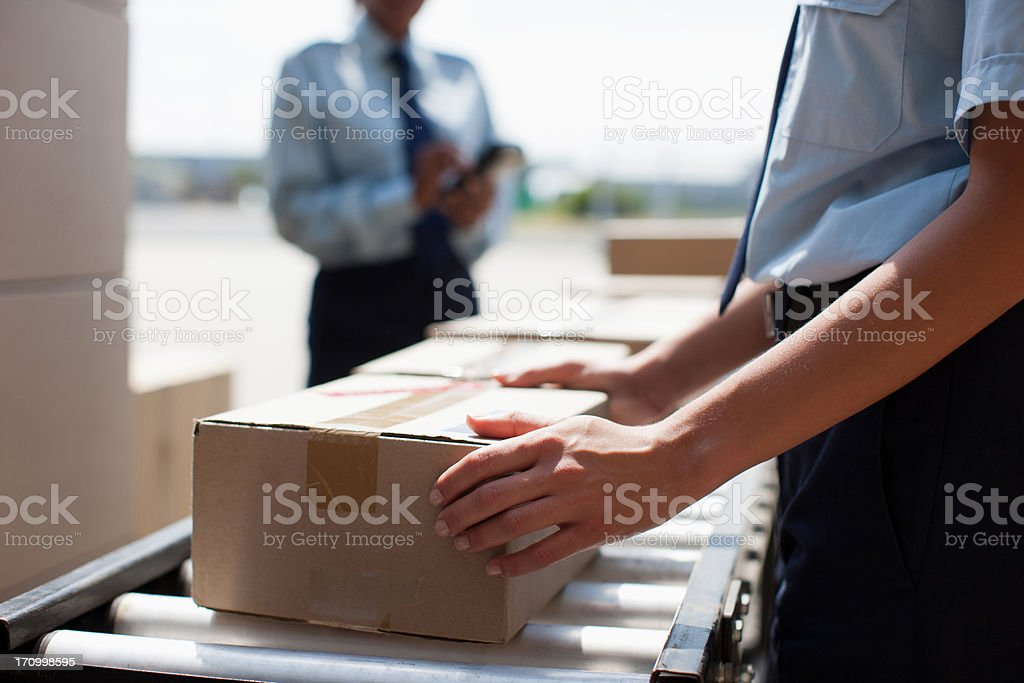 Worker taking box from conveyor belt in shipping area stock photo