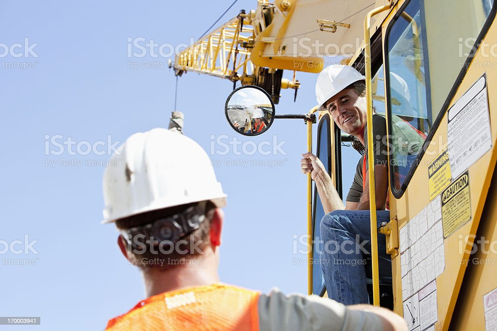 Worker talking to crane operator stock photo