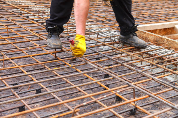 Worker ties steel reinforcing bars with wire. The worker ties steel reinforcing bars with wire to strengthen the foundation. Close-up. Daylight. rod stock pictures, royalty-free photos & images