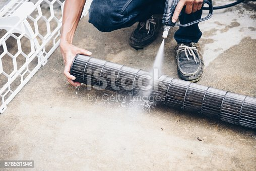 istock Worker to cleaning coil cooler of air conditioner by water for clean a dust on the wall in customer home when maintenance service 876531946