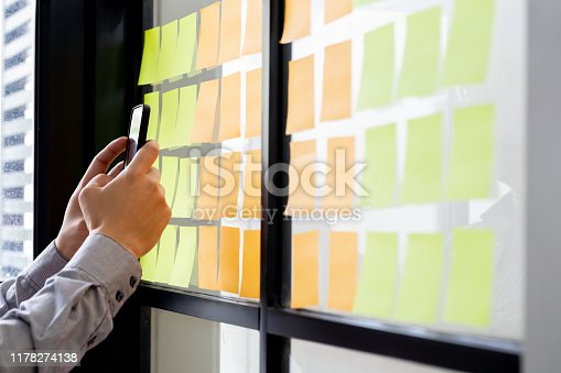 1059655118 istock photo IT worker tracking his tasks on kanban board in mobile phone application. Using task control of agile development methodology. Man attaching sticky note to scrum task board in the office 1178274138