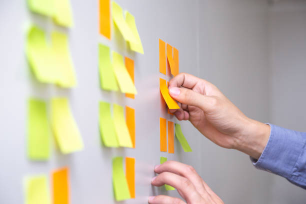 IT worker tracking his tasks on kanban board. Using task control of agile development methodology. Man attaching sticky note to scrum task board in the office stock photo