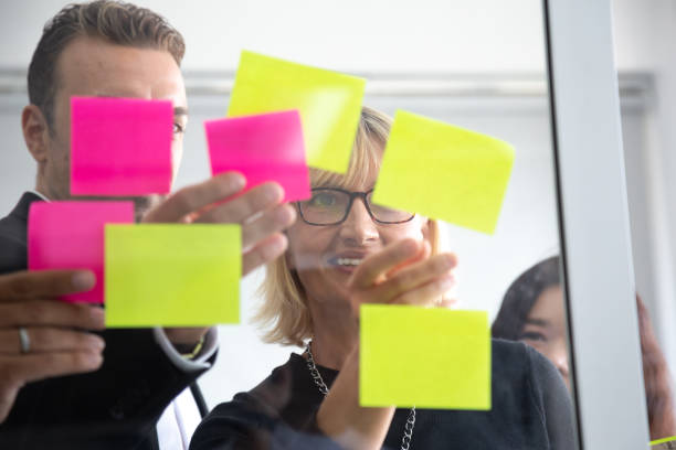 it-mitarbeiter verfolgen seine aufgaben auf kanban-board. verwendung von task-control der agilen entwicklungsmethodik. teammitglieder, die klebrige notizen an scrum task board im büro anhängen - mobilität stock-fotos und bilder