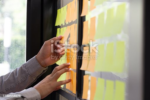 1059655118 istock photo IT worker tracking his tasks on kanban board. Using task control of agile development methodology. Man attaching sticky note to scrum task board in the office 1188558926
