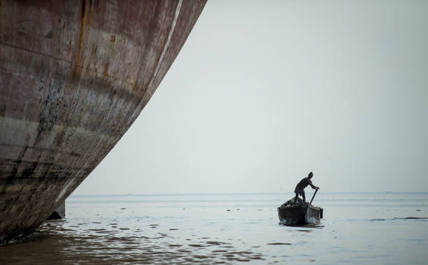 worker travelling in a small boat in  Bangladeshi ship breaking yard stock photo