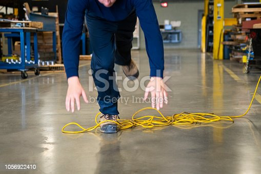 An industrial safety topic.  A worker tripping over an electrical extension cord in an industrial environment.