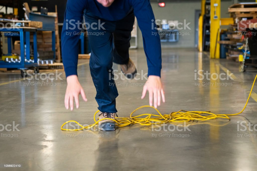 A worker tripping over an electrical cord in an industrial environment stock photo