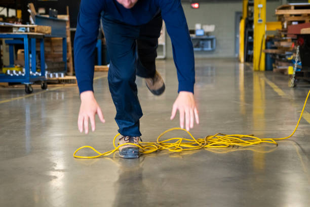 A worker tripping over an electrical cord in an industrial environment An industrial safety topic.  A worker tripping over an electrical extension cord in an industrial environment. misfortune stock pictures, royalty-free photos & images