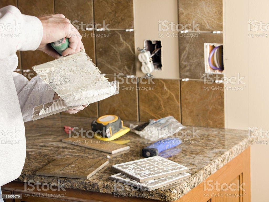 Worker Troweling Morter on Tile for New Kitchen Backsplash stock photo