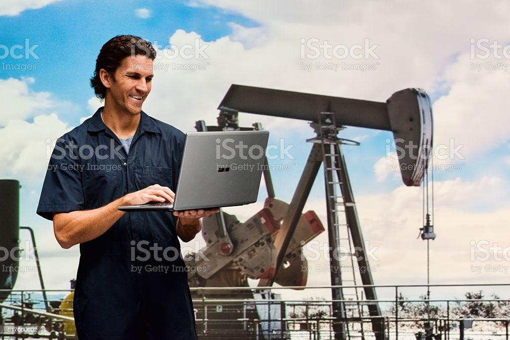 Worker typing on laptop in oil industry stock photo