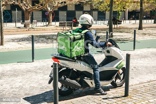 istock worker Uber Eats on the scooter delivers food to customers. 953979734