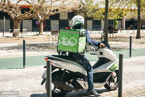 istock worker Uber Eats on the scooter delivers food to customers. 955264224