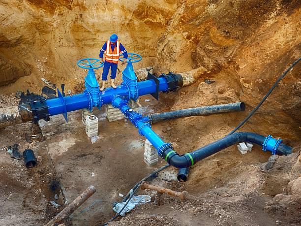 Worker underground on gate valve, reconstrucion of drink water system stock photo