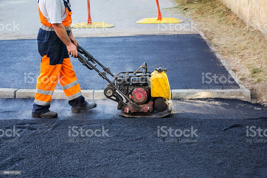Worker use vibratory plate compactor stock photo