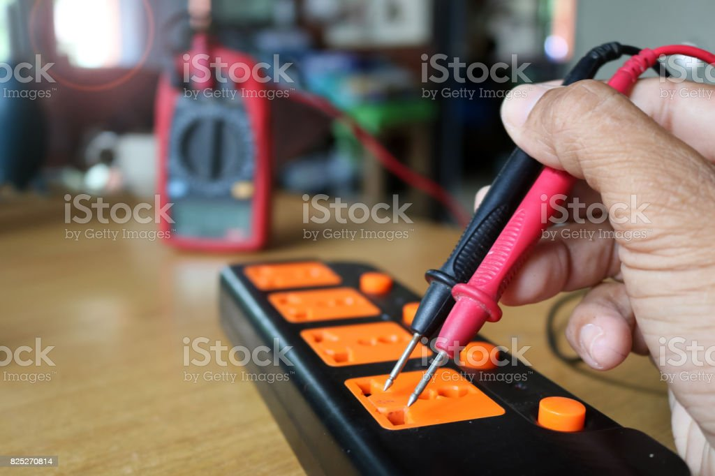 Worker use voltmeter measure the current from extension plug stock photo