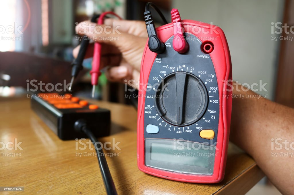 Worker use voltmeter measure the current from extension plug. stock photo