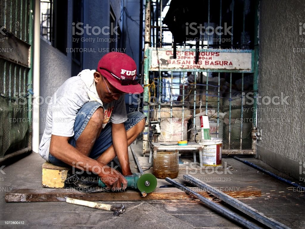 A worker uses a grinder to trim a metal rod stock photo