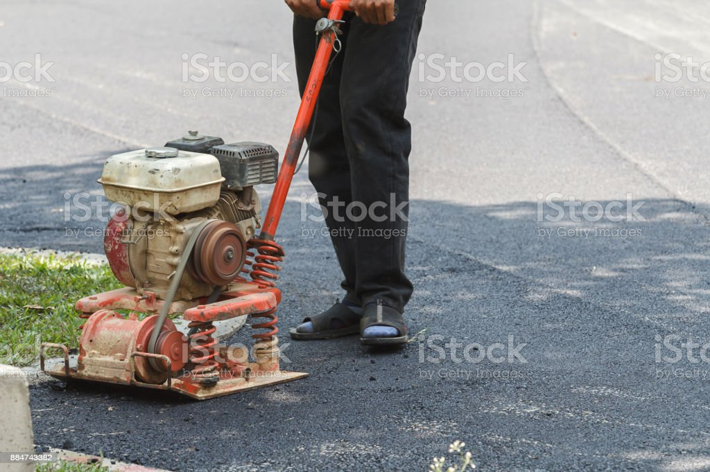 Worker uses vibratory plate compactor compacting asphalt at road repair stock photo