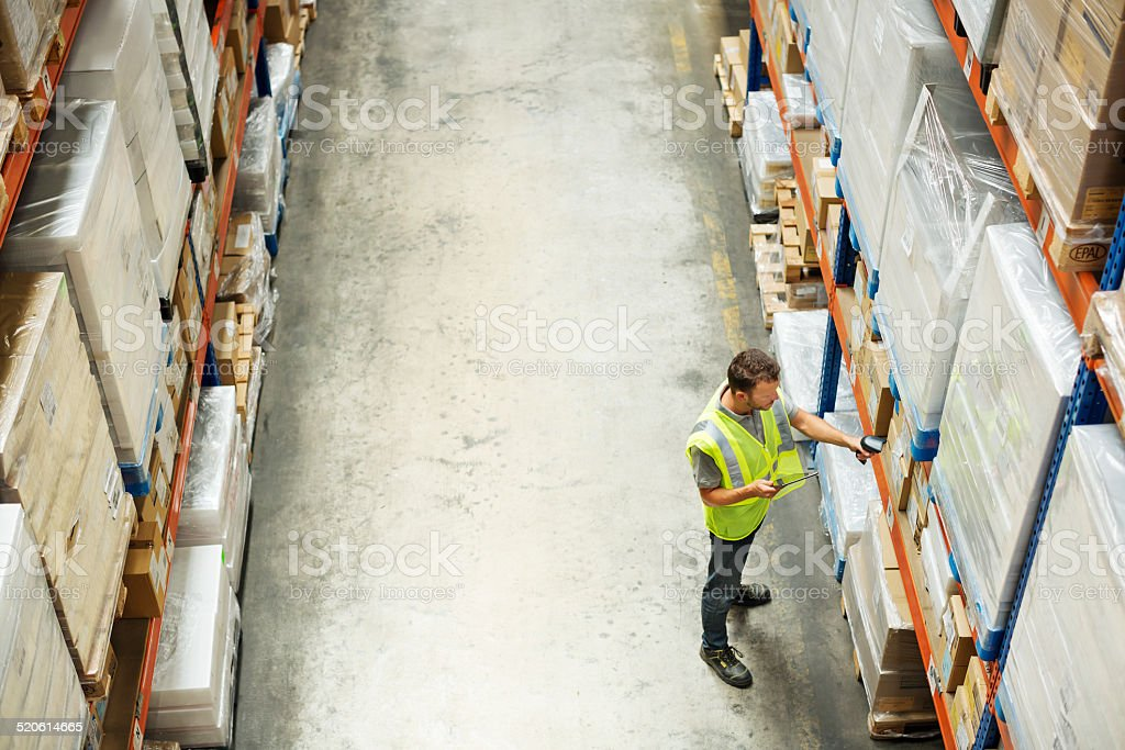 Worker using barcode reader at warehouse stock photo