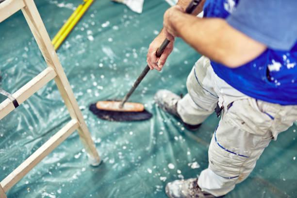 Arbeiter mit Besen für die Reinigung von Schmutz während der Renovierung des Hauses. – Foto