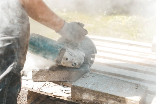 Worker using circular saw for cutting concrete block for road or pavement construction