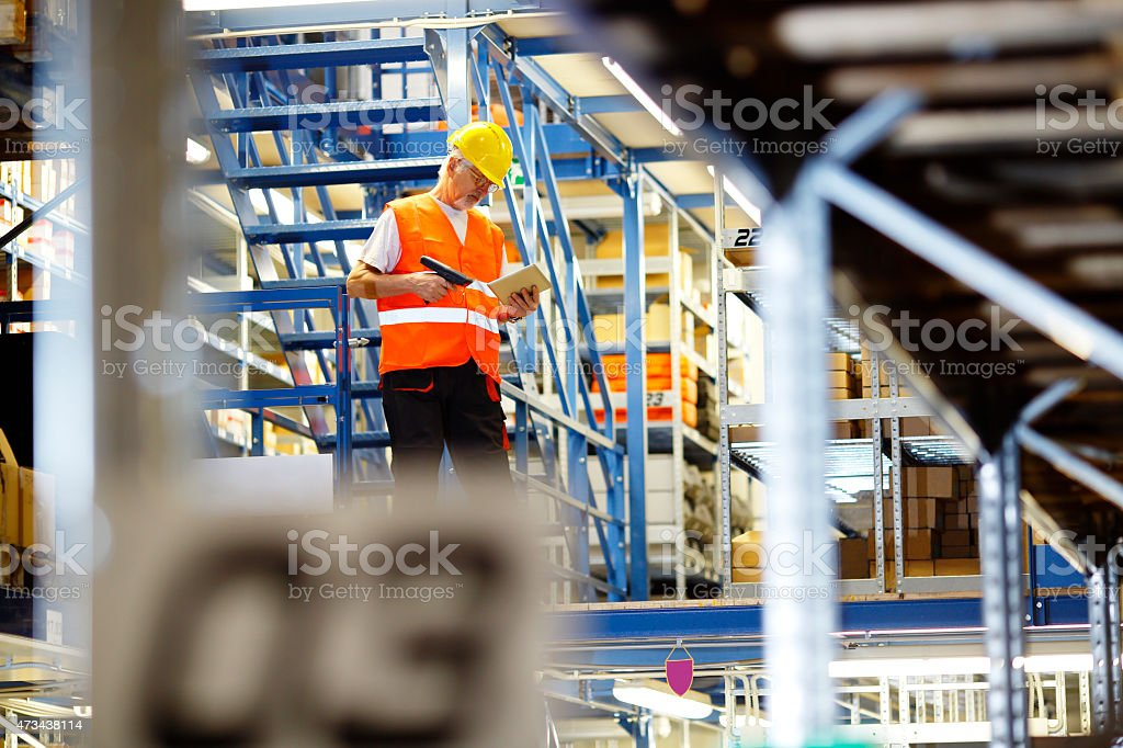 Worker using digital tablet at warehouse stock photo