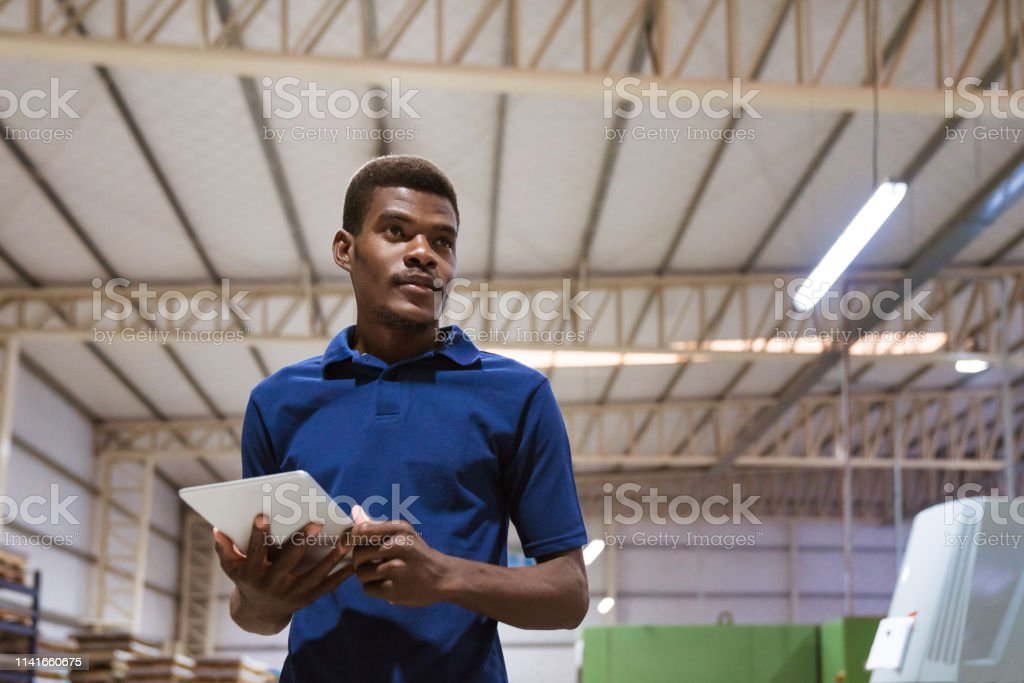 Worker using digital tablet in industry Male worker looking away while holding digital tablet. Confident young trainee is standing in industry. He is wearing blue t-shirt. 25-29 Years Stock Photo