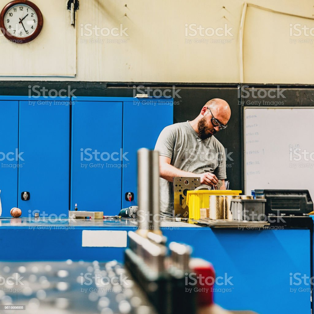 Worker Using Drill in Factory stock photo