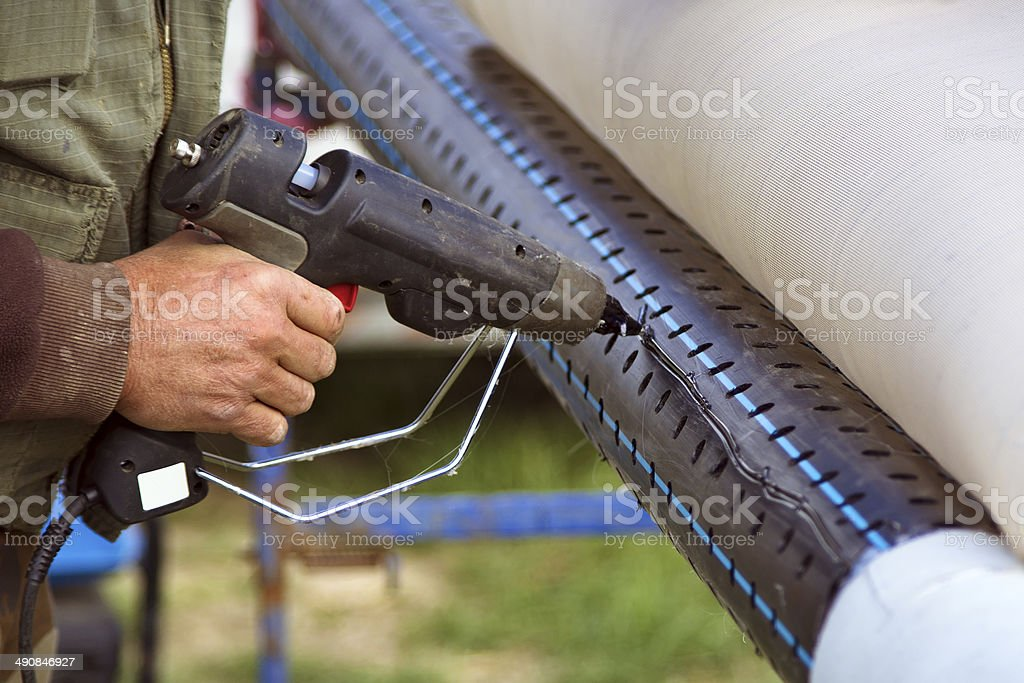 Worker using hot plastic glue gun on tube stock photo