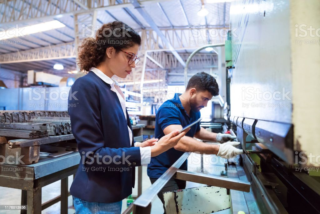 Worker using machinery by manager in factory Production worker using machinery while female manager holding digital tablet. Expertise are related to manufacturing occupation. They are in factory. 20-24 Years Stock Photo