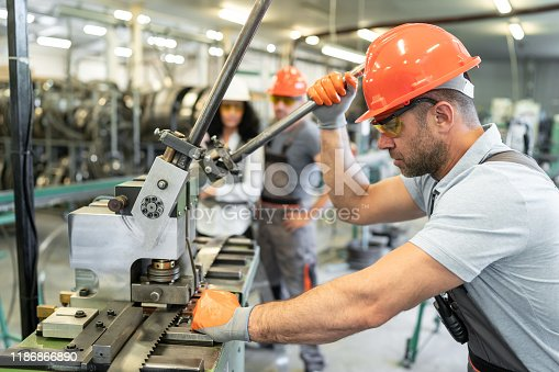Worker using machinery in a factory