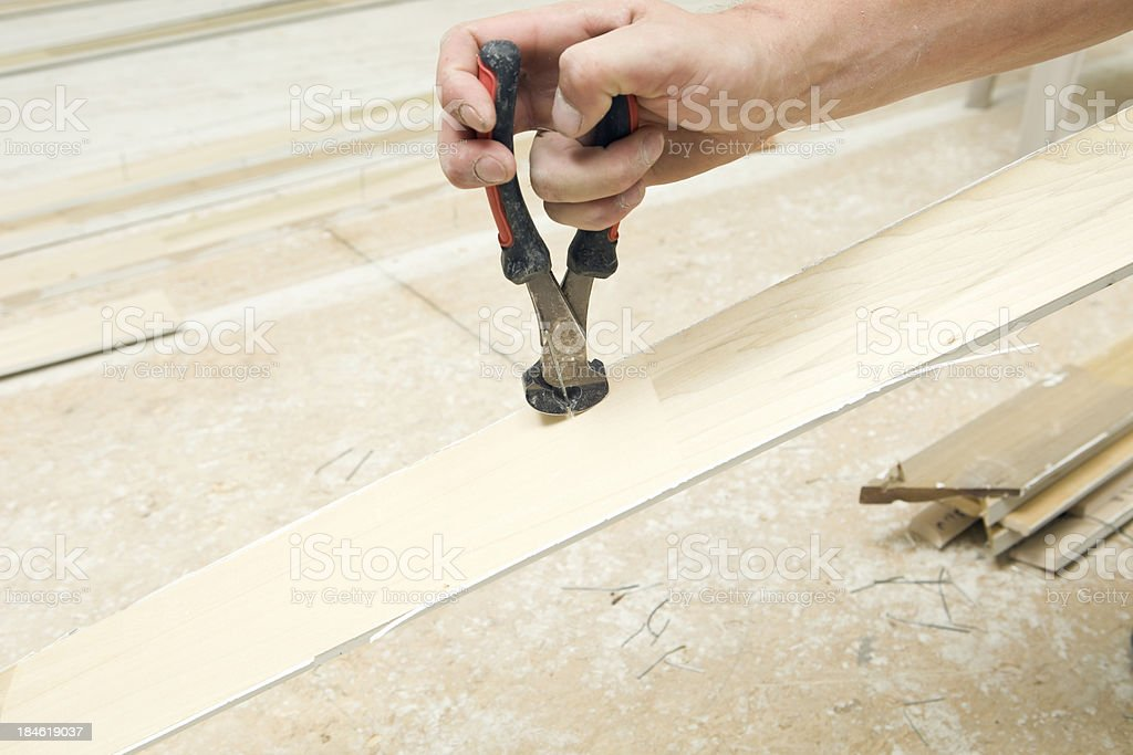 Worker Using Nail Puller on Trim Board stock photo