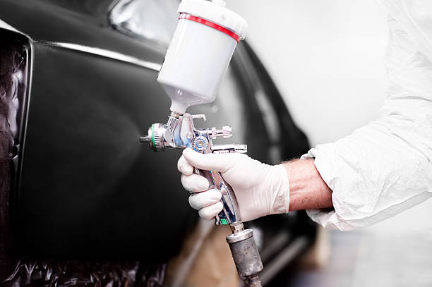 worker using paint spray gun for painting a car - auto body repair stock photos and pictures