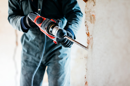 Mature worker demolishing wall with drill at house
