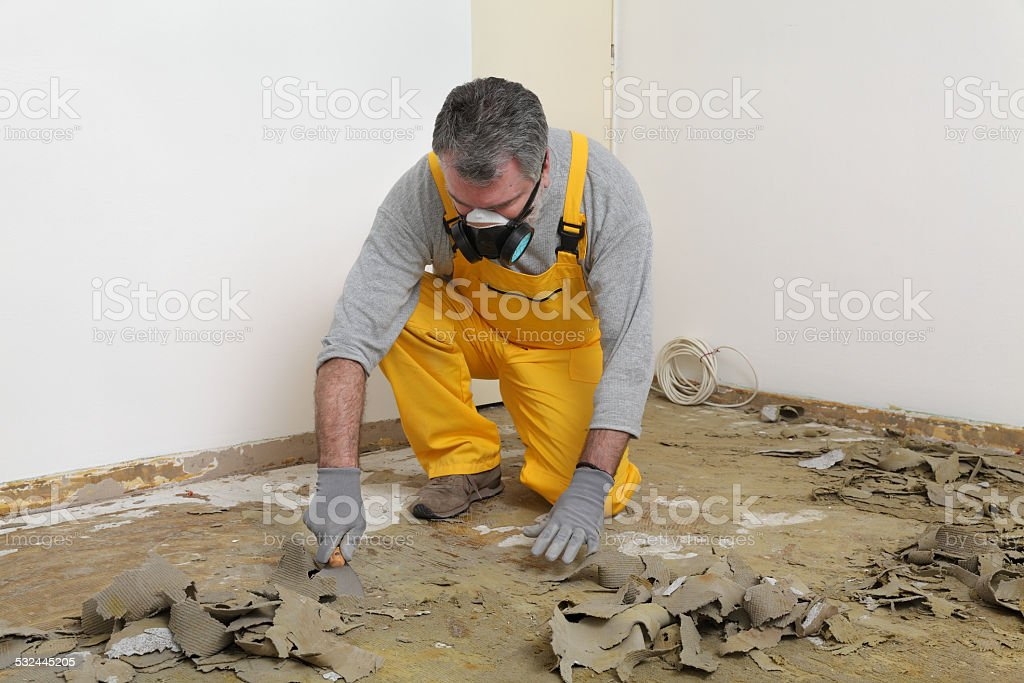 Worker using putty knife for cleaning floor stock photo