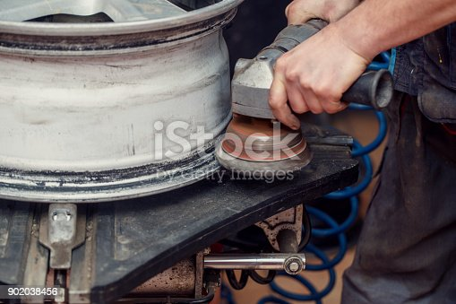 498888104 istock photo Worker using tire grinder machine for tire wheels 902038456