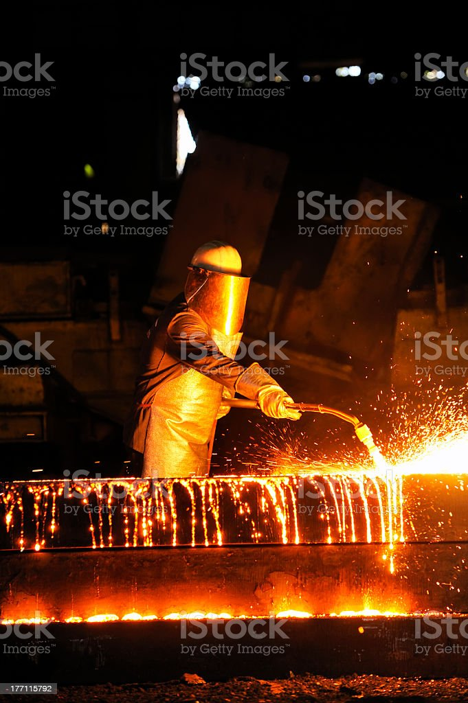 worker using torch cutter to cut through metal royalty-free stock photo