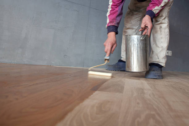 Worker Varnishing Lacquering a Parquet Worker varnishing lacquering an oak parquet floor by paint roller first layer after polishing. lacquered stock pictures, royalty-free photos & images