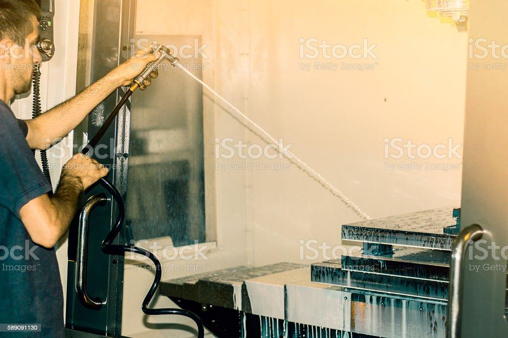 Worker washing CNC machine after finished job. stock photo