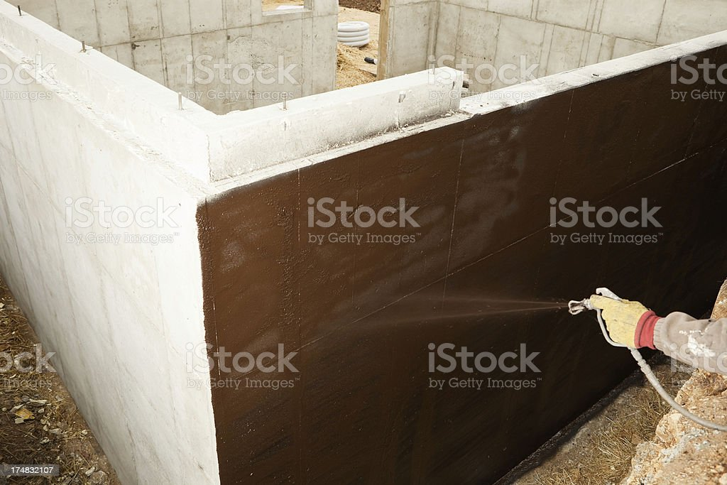 Worker Waterproofing a new House Foundation royalty-free stock photo