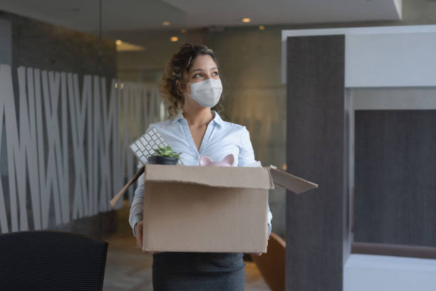 Worker wearing a facemask at the office while holding a box with her belongings after being fired stock photo